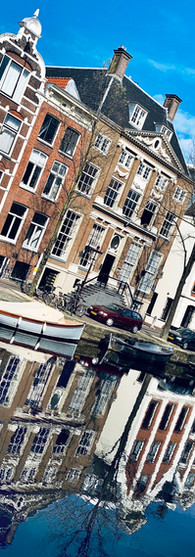 beautiufl canal houses at grimburgwal amsterdam on crisp spring morning with blue sky