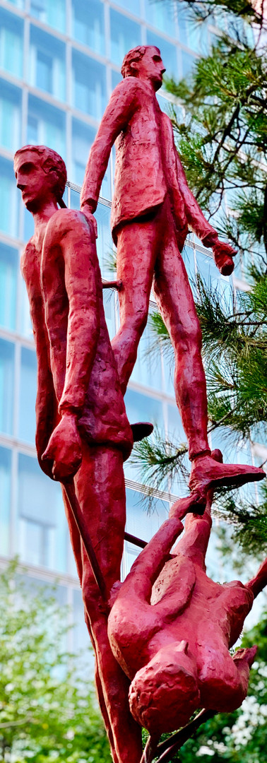 three red men above each other in sculpture world trade center amsterdam with office building in background amsterdam zuidas