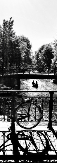 couple in boat in canal leidsegracht under the bridge iphoneonly