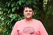 Audiodescrição: Foto de Leonardo. Ele sorri. É branco, tem o cabelo preto e curto. Usa uma camiseta rosa com o desenho de um cérebro. Ao fundo há uma parede de plantas verdes.
