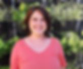 Audiodescrição: Foto de Mayla. Ela é vista do busto para cima e sorri. É branca, tem os cabelos lisos, curtos e castanho escuro. Usa uma camiseta salmão.  Ao fundo há plantas verdes.