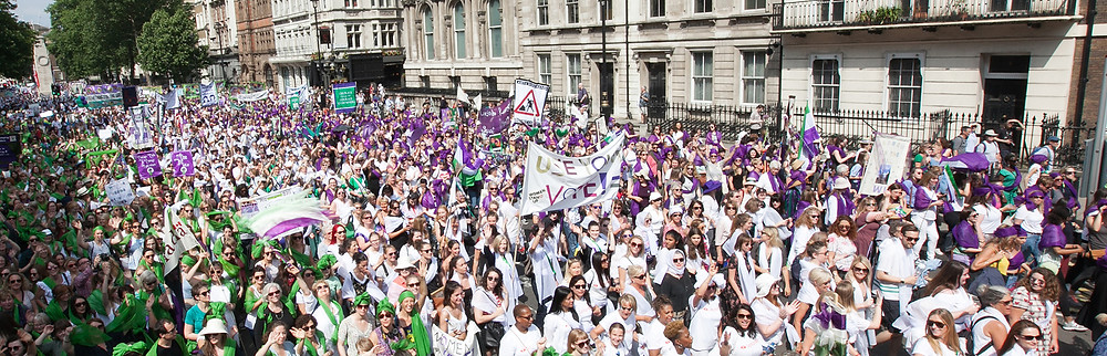 A mass of women dressed in suffragette colours recreating a march