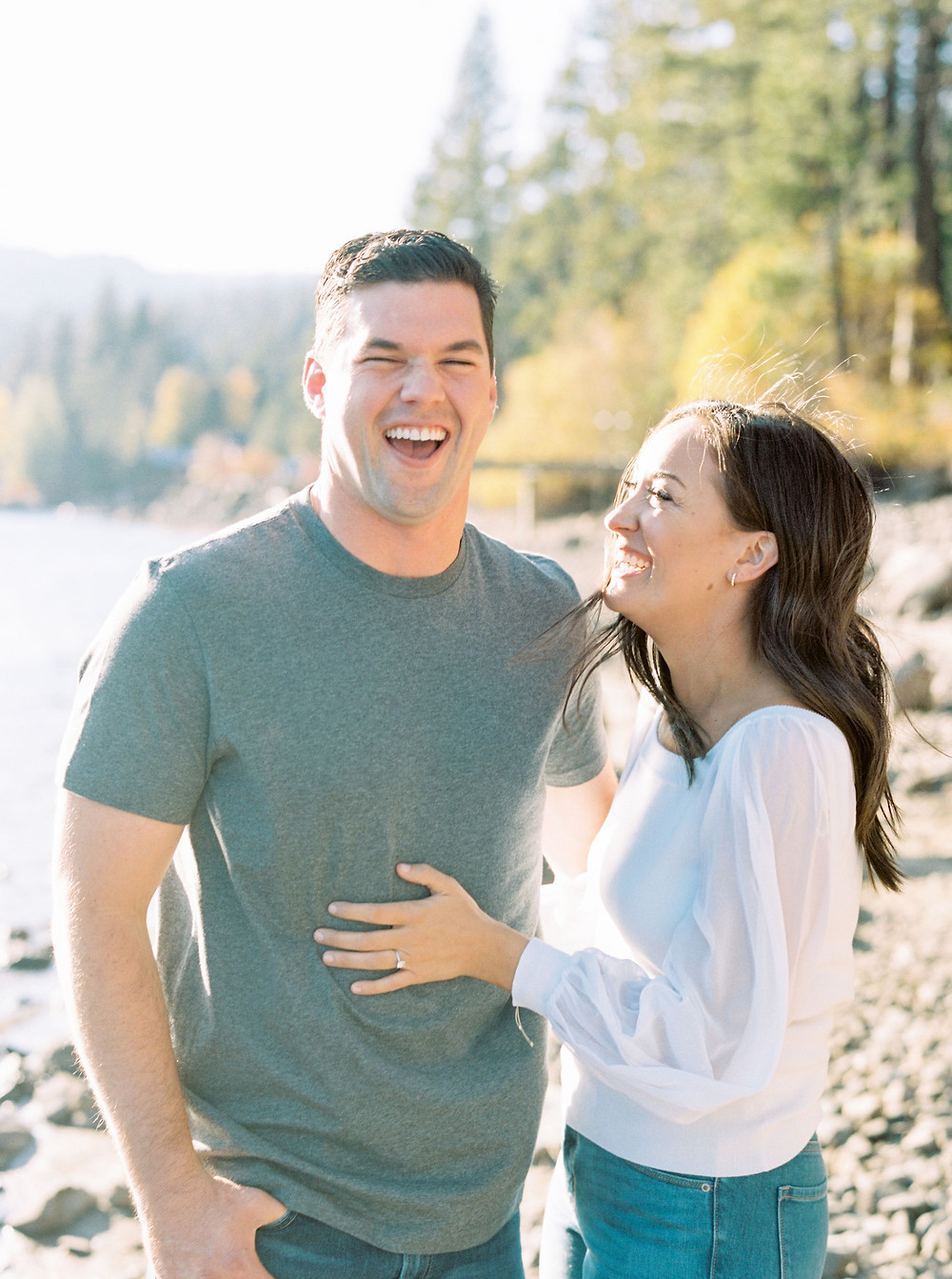 Engaged couple laughing on beach at Lake Tahoe