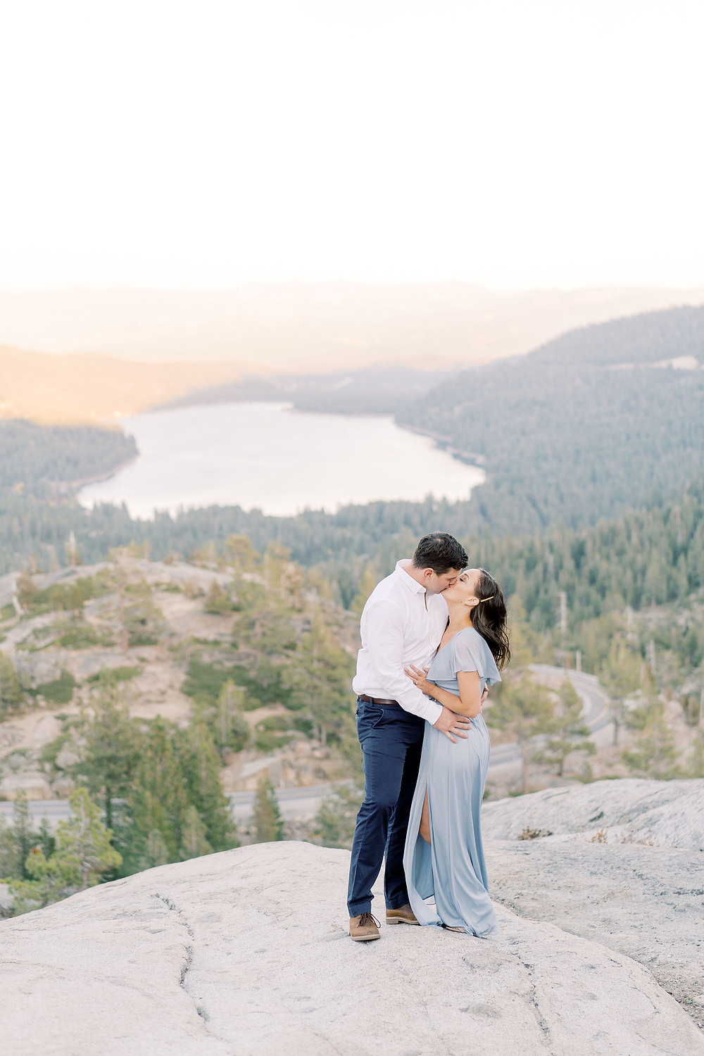 Engaged couple on mountain overlooking Lake Tahoe
