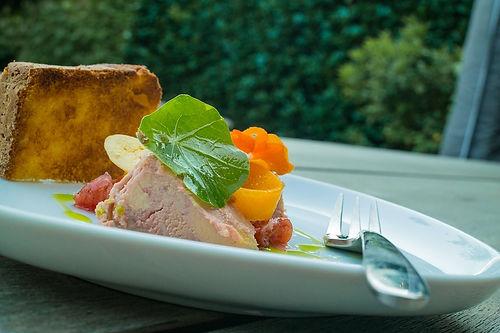 Du foie gras dans une assiette blanche où on peut également voir de l'huile, une fourchette, des herbes ainsi que des arbres en arrière-plan