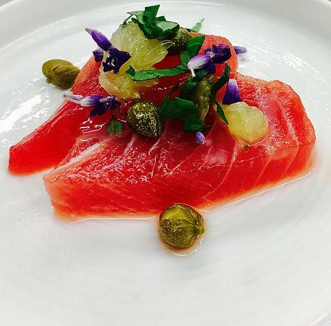 Un tataki de thon rouge dressé dans une assiette accompagné de fruits, herbes et fleurs pour la décoration