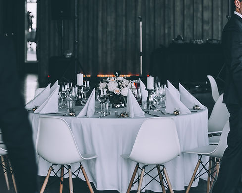 La table d'hôtes du traiteur les 3sens pour des repas d'entreprise ou familiaux.Un couvert dressé pour un dejeuner d'affaires dans une pièce aux murs sombres. Les chaises, la nappe ainsi que les serviettes sont blanches. On a un bouquet de fleurs ainsi que des bougies au milieu de la table