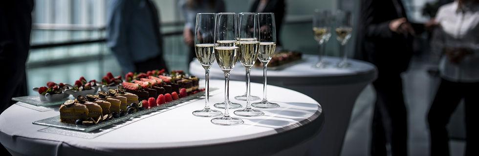 Sur une table ronde blanche, des coupes de champagnes remplies sont posées et il y a sur la gauche des plats avec des desserts au chocolat, à lafraise ainsi qu'à la framboise