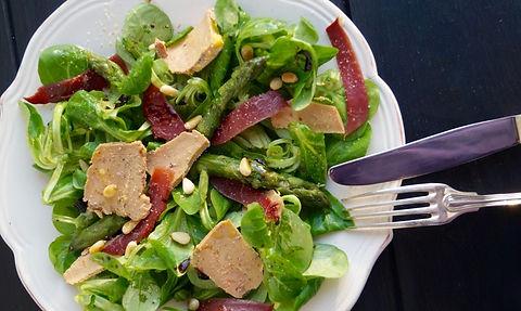 Salade dans une assiette composée de feuilles de salade, de mroceaux de foie gras ainsi que de magret de canard. On distingue également des petites graine et des couverts sur le bord de l'assiette
