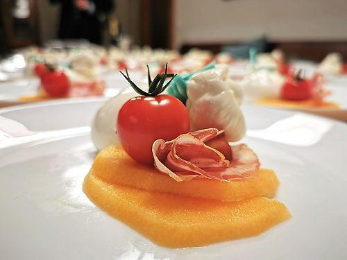 On peut voir des tranches de melon sur lesquelles sont déposées du jambon cru ainsi qu'une tomates. Il y a beaucoup d'assiettes du même type en arrière-plan