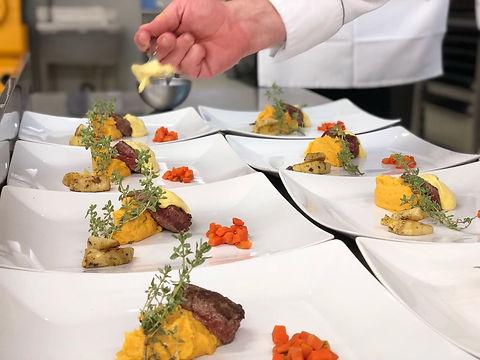 Des assiettes dressées et prêtes à être servies. On peut voir de la viande rouge accompagné d'une purée jaune et de carottes découpées en brunoise