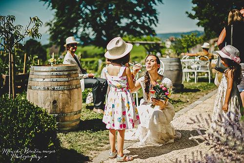 La mariée avec un verre de vin et un bouquet à la main est entrain de souffler du savon pour faire des bulles devant une petite filles avec une robe blanche à motifs et un chapeau. Des tonneaux sont là pour la décoration et il y a des tables et chaises blanches oû l'on peut voir un homme assis avec un chapeau, des lunettes de soleil et un blazer