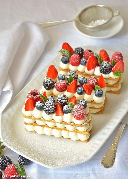 Un mille-feuille possédant trois étages de crème blanche et sur le dessus des fruits rouges, à savoir fraises, framboises, myrtilles et mûres