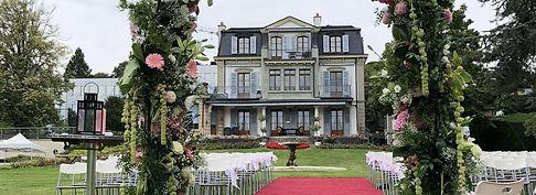 Le Centre Général Guisan à Pully peut accueill des événements. Composé de trois étages avec de grandes fenêtres et des balcons. Il y a des parterres de fleurs rouges et vertes devant. Le jardin est préparé pour un mariage en témoigne les rangées de chaises blanches séparées en deux groupes par un tapis rouge qui passe au milieu