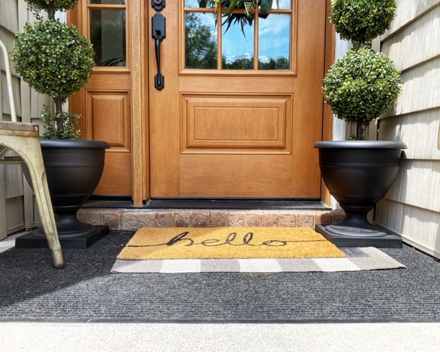 Create a larger space by layering an outdoor rug that is larger than your front door