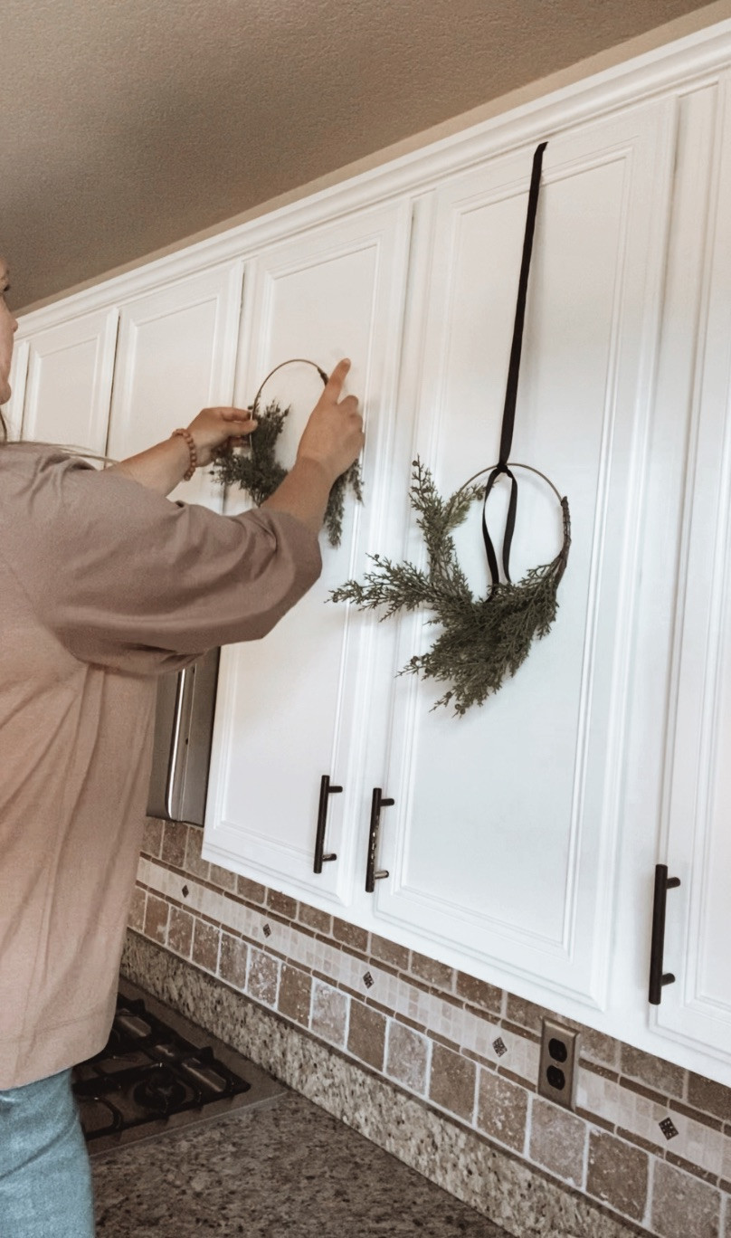 Easy and money saving ways to hang mini wreaths on kitchen cabinet doors.