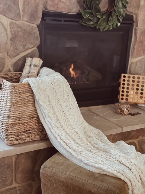 Styling a fireplace with decorations like a blanket, wood log, and board games.