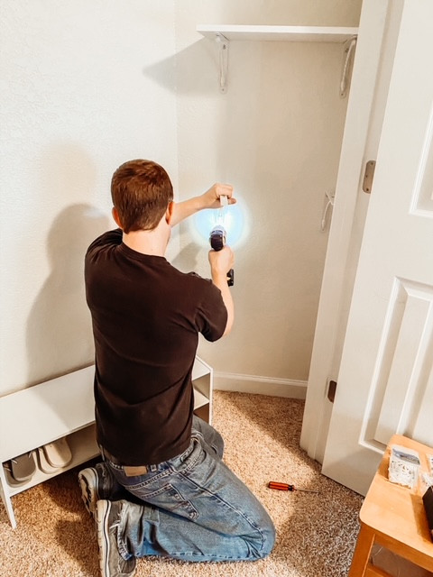 Installing white laminate closet shelves.