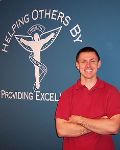 """Dr. Zac Parry standing in front of the HOPE Chiropractic mural stating the clinic mission statement: """"Helping Others by Providing Excellence.""""  This sums up what we do at HOPE Chiropractic, helping those suffering with many ailments with safe, gentle and effective Atlas Orthogonal Chiropractic.  Fibromyalgia, Fatigue, Chronic Fatigue, Always Tired, Tired, Chronic Fatigue Syndrome, CFS, Migraine, Migraines, Headache, Headaches, Head Pain, Migraine Headaches, Migraine Relief, Headache Relief, Tension Headache, Tension Headaches, Migraine Headaches, Migraine Headaches Relief"""