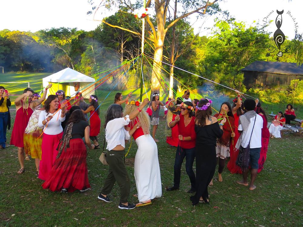 Mulheres e homens dançando em volto do mastro de fita