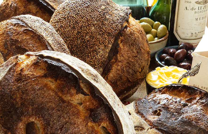 Several Artisan Sourdough loaves arranged with olives, wine and butter