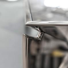 Mobile basso triangolare in acciaio a specchio con piano in vetro retroverniciato, particolare finiture
