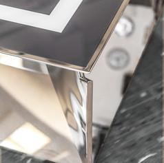 Mobile basso in acciaio a specchio con piano in vetro retroverniciato, particolare finiture