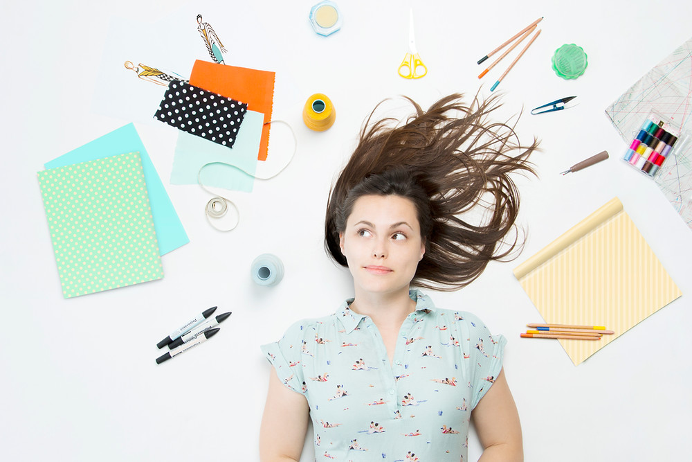 woman thinking about creative ideas with notebook, pens, pencils, threads, craft tools