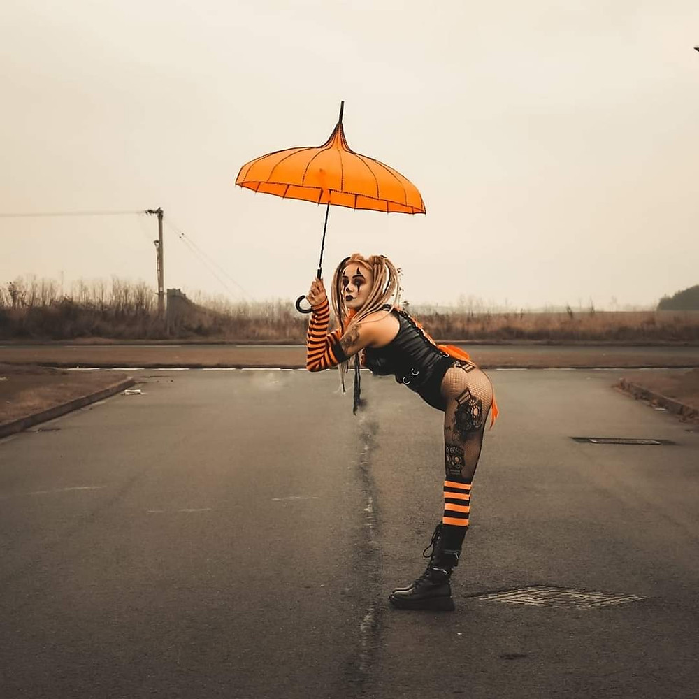 female clown in fishnets bends over with an umbrella