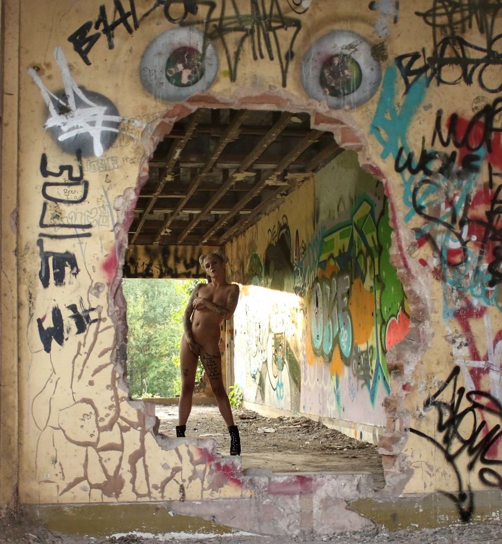 Nude woman with tatoos poses nude, urbex