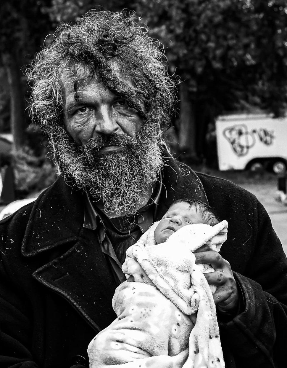 Photograph of a homless man holding a newborn baby