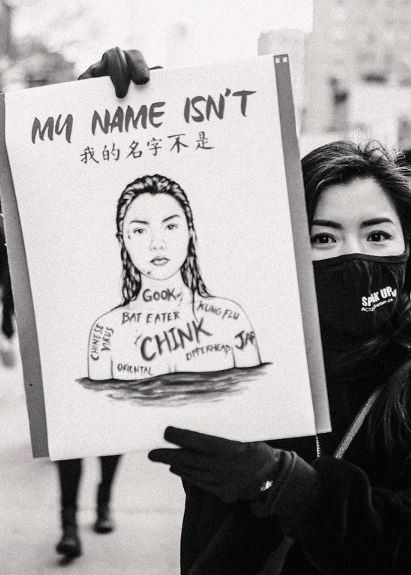 Asian woman holds up sign during anti-Asian violence protest.