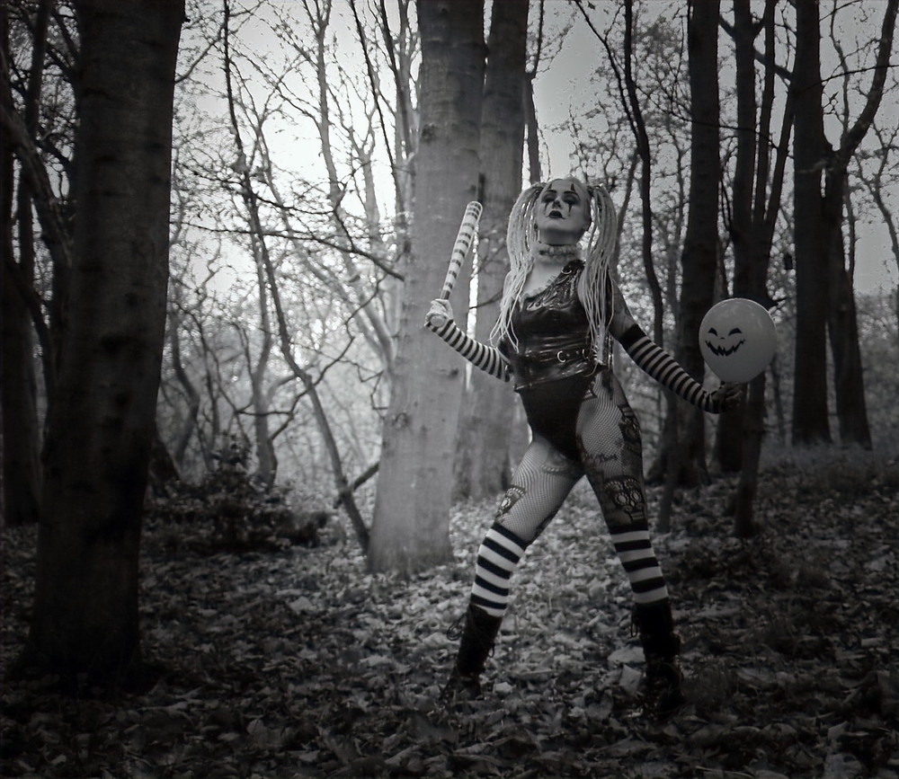 Slutty the clown poses in fishnets in the woods