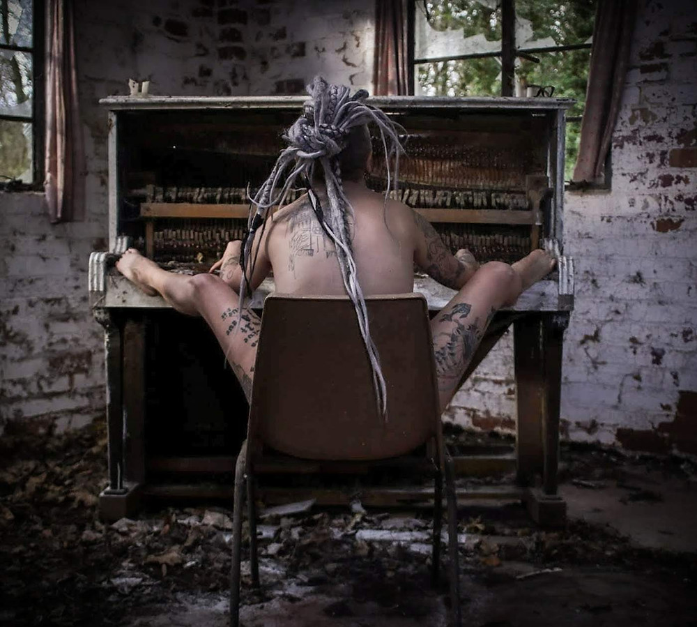 Slutty the clown opens her legs and plays the piano in the nude in an abandoned building