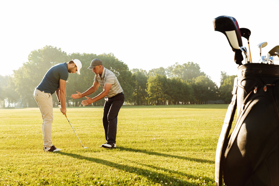 young-sportsman-practicing-golf-with-his-teacher.jpg