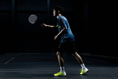 128563782-asian-badminton-player-is-hitting-in-court.jpg