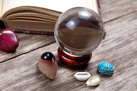 שולחן עץ ועליו כדור בדולח, ספר ואבנים טובות