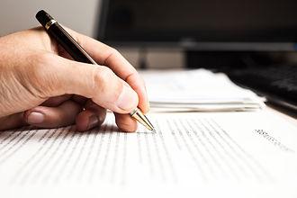 יד מחזיקה עט וכותבת על נייר