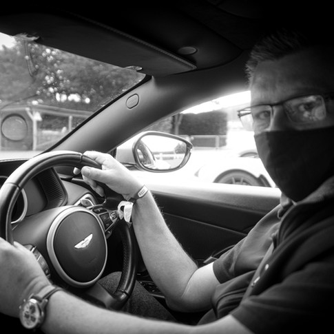 Vinnylondon at the helm of an Aston Martin