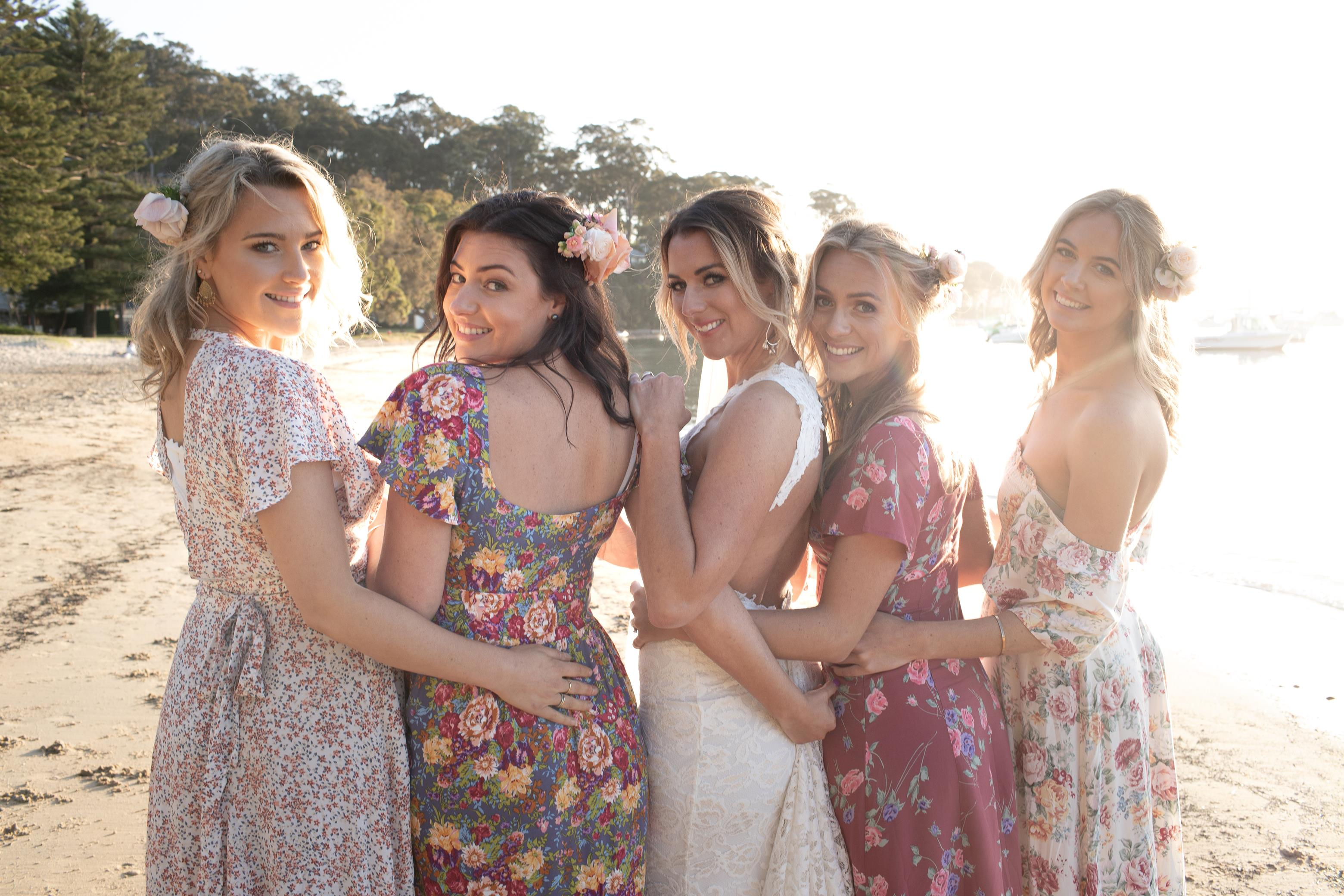 Photoshoot of bride and bridesmaids turning around in floral dresses