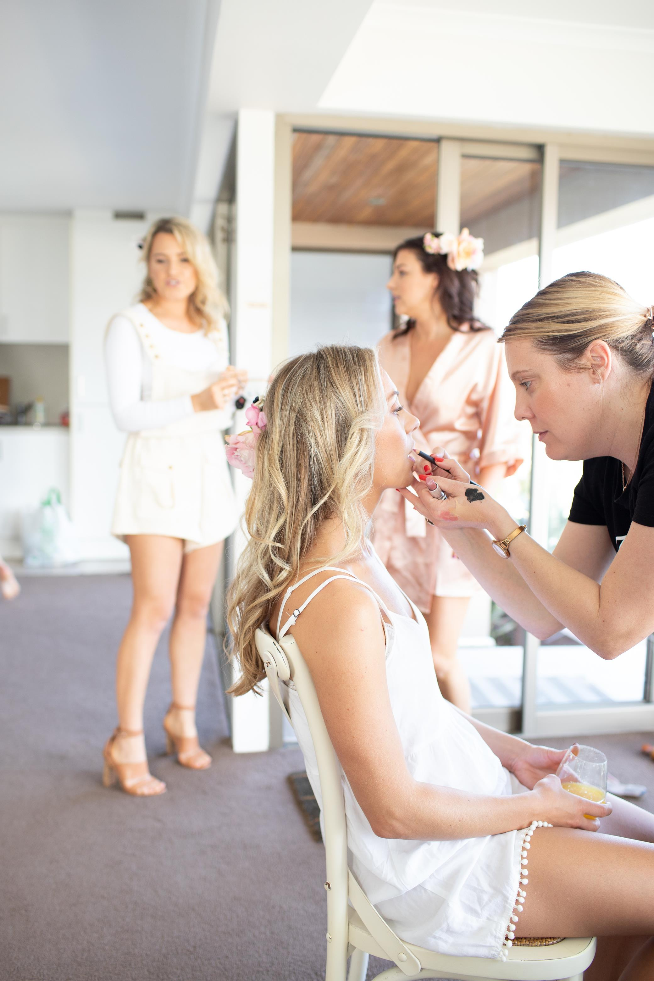 Makeup Artist applying lipstick on bridesmaid