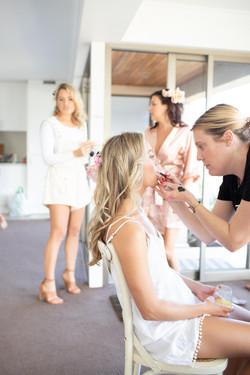 Makeup Artist applying lipstick on bridesmaid