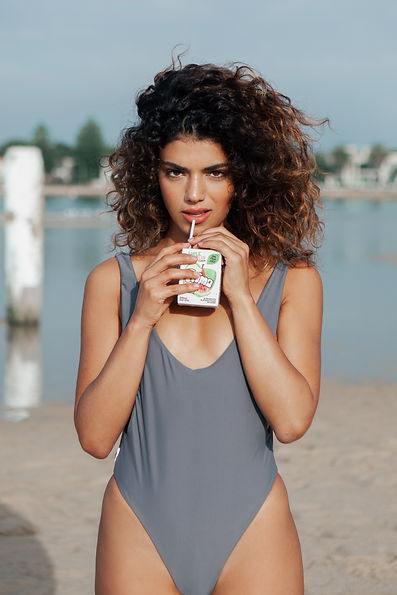 model sipping juicebox wearing grey swimsuit