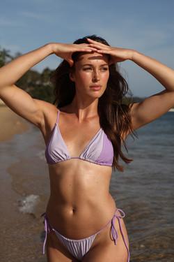 Model posing in purple bikini