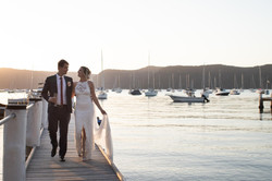 Bride and Groom walking along wharf at Clareville
