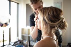 Makeup Artist applying makeup on Bride