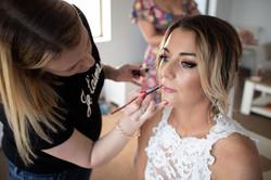 Makeup Artist applying lipstick on Bride