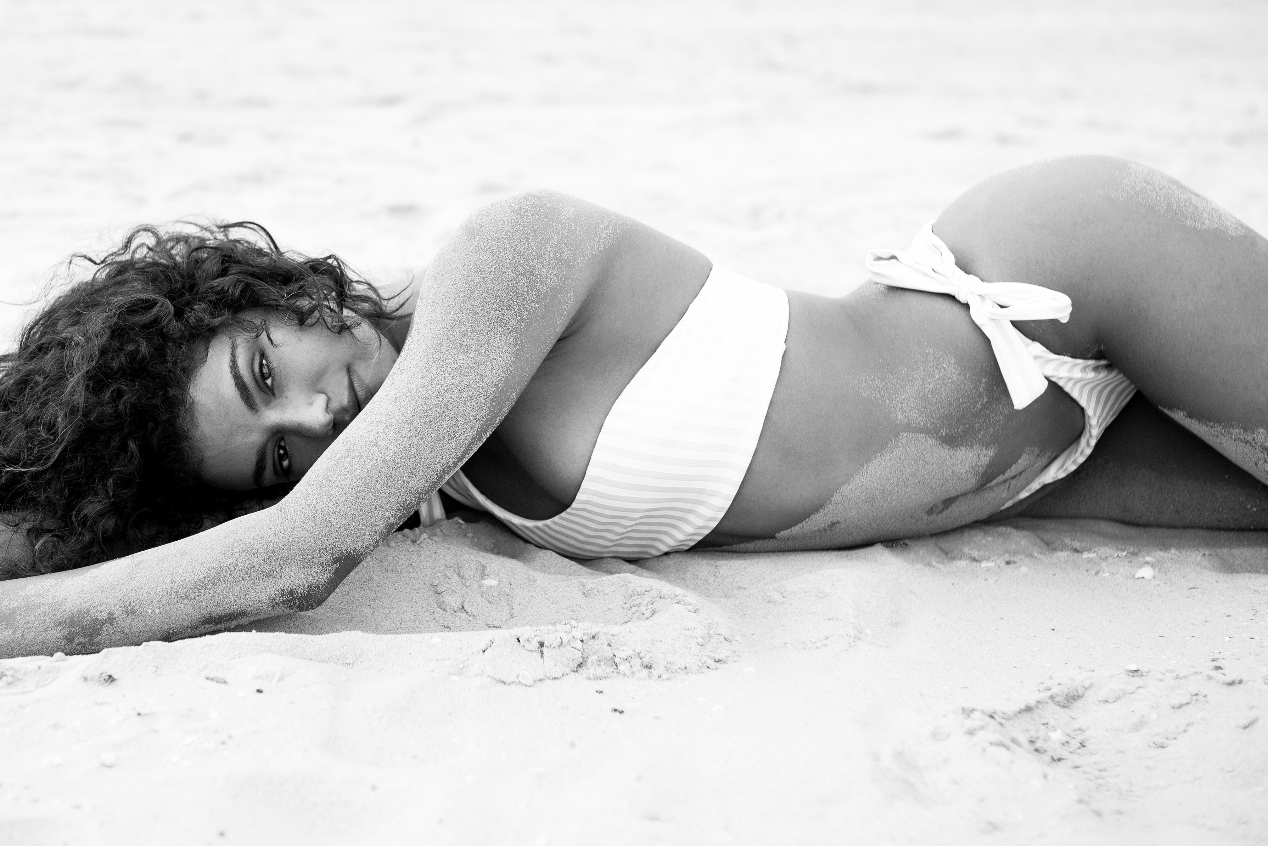 Model lying in sand in bikini photoshoot