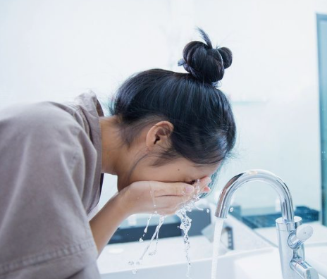 Woman washing face in sink