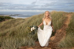 Bride walking on sand dunes with bouquet